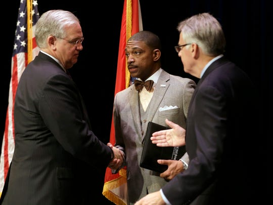 Missouri Gov. Jay Nixon, left, shakes hands with Rev. Starsky Wilson, center, and Rich McClure, right, after swearing the two men in as co-chairs of a 16-member commission Tuesday, Nov. 18, 2014, in St. Louis. The independent commission has been created to study issues that have surfaced since the fatal police shooting of Michael Brown. (AP Photo/Jeff Roberson)