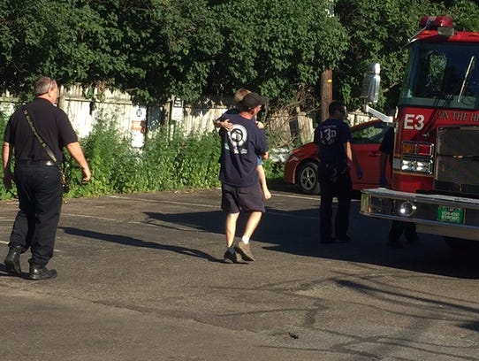 A child is carried toward a Burlington fire truck near