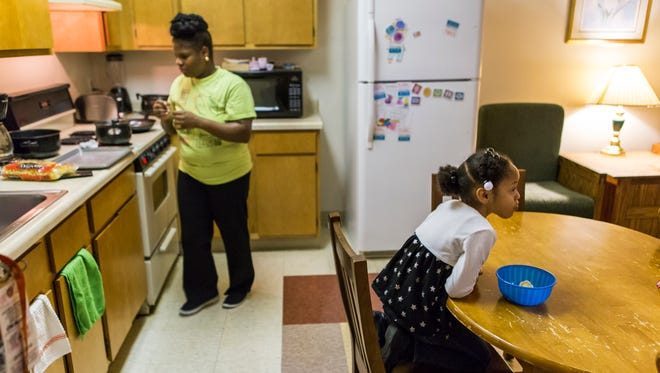Shannel Coverdale cooks dinner as her six year-old daughter Tierra Foeman has a snack at the kitchen table in their apartment at the YWCA in Wilmington's West Center City neighborhood on Wednesday afternoon.