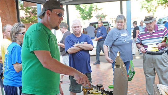 Arrin Plowman grills zucchini and squash during the Market to Menu event at the Wichita Falls Downtown Farmers Market in this file photograph. Restaurateurs will be at the market 9 a.m. June 17 cooking dishes using fresh produce.