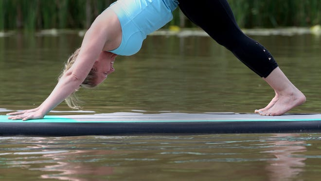 Amy Gurske from Pittsford balances a downward dog yoga pose.
