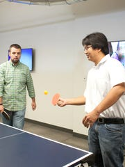 Engineers Jason McKee, left, and Simon Lee play a game of ping-pong during a tour of Humana's new Digital Experience Center to show how employees can walk away when stuck on a task-oriented problem and gain a fresh perspective while exercising.