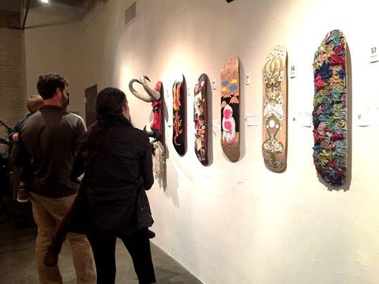 Guests at The Parliament's third annual Decked Out fundraiser look at hand-painted, collaged and manipulated skate decks on display at The Bond in York Saturday night. More than 130 skate decks from six Central Pa. art galleries were auctioned off.