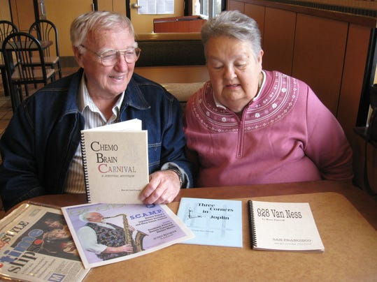 Purcells MAIN ART Ross and Carol with some of his books, news articles.jpg
