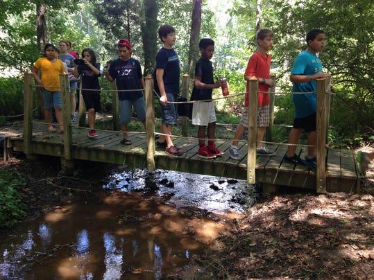 Millbrook Middle students cross stream.JPG