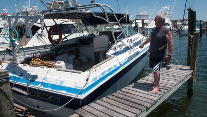 Wayne Benson tends to his damaged boat at Southwind Marina on Tuesday, May 2, 2017. The 63-year-old was injured during Sunday night's storm after his boat broke from its moorings and tossed him into the water.