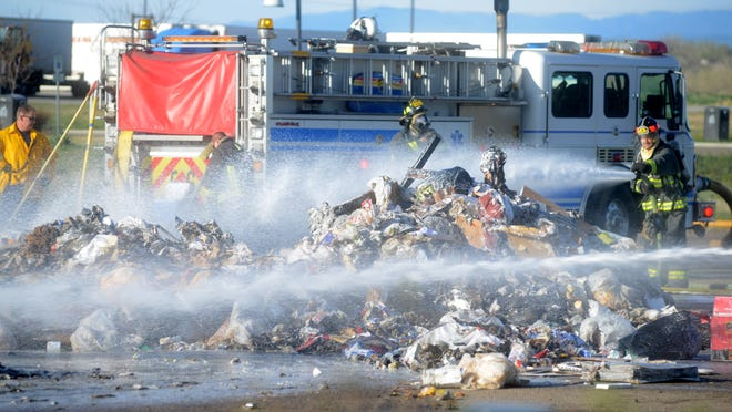 Poudre Fire Authority firefighters douse a smoldering pile of trash dumped in the parking lot of the Colorado Visitors Center on East Prospect Road on Tuesday morning. The trash was dumped by a Waste Management driver who discovered the fire in the back of his truck as he was driving.
