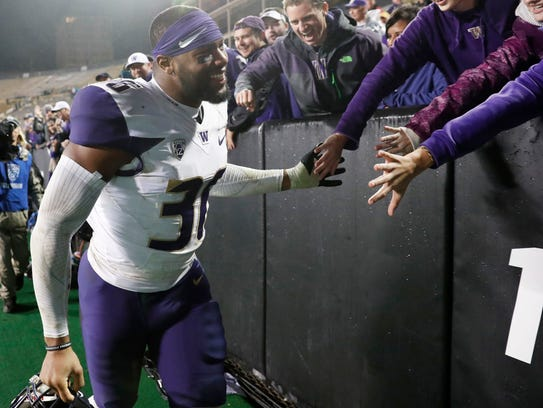 Washington linebacker Azeem Victor celebrates with