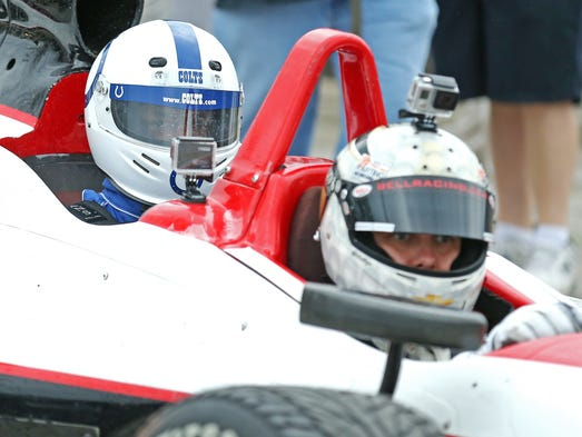 Indianapolis Colts wide receiver Reggie Wayne arrives in a two-seater IndyCar driven by Indianapolis 500 pole sitter Ed Carpenter on the first day of training camp, on Wednesday, July 23, 2014, at Anderson University.