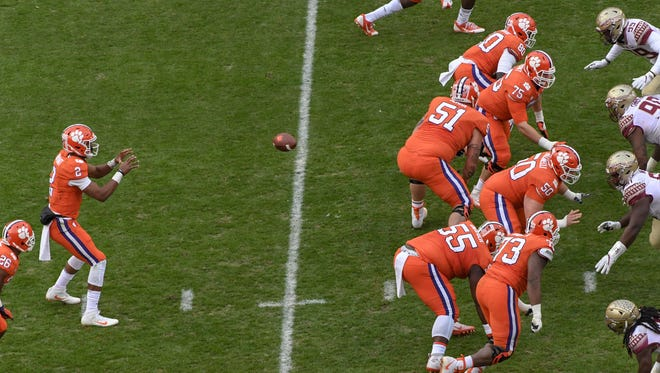 Clemson quarterback Kelly Bryant(2) takes a snap from defensive tackle Justin Falcinelli (50) while offensive linemen protect him playing Florida State during the first quarter in Memorial Stadium at Clemson on Saturday.