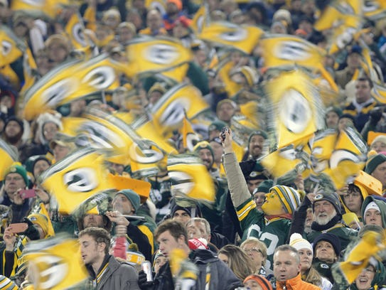 Green Bay Packers fans wave flags during a 2014 game