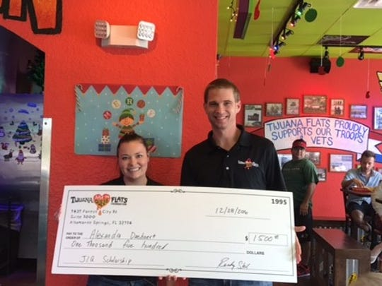 Randy Steil, (right), executive director of the Tijuana Flats Just In Queso Foundation, gives a $1,500 check to Florida Gulf Coast University senior Alexandra Doehnert.