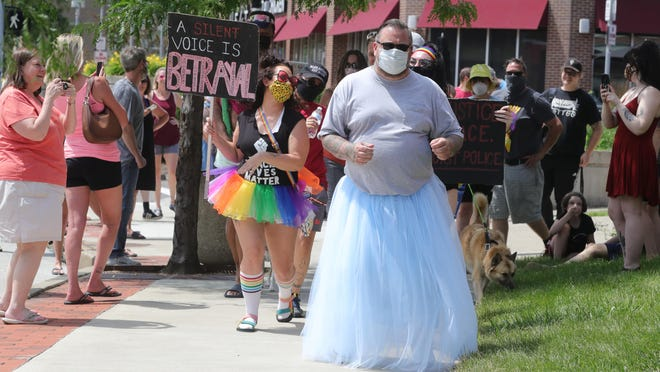 "Arkham Tattoo owner Eric Starr ""prancercises"" down Market Street in Highland Square dressed in a tutu followed by a group of supporters on Sunday, June 28, 2020, Akron, Ohio. Starr lost a bet which helped raise around $3,000 for the Akron-Canton Regional Foodbank."