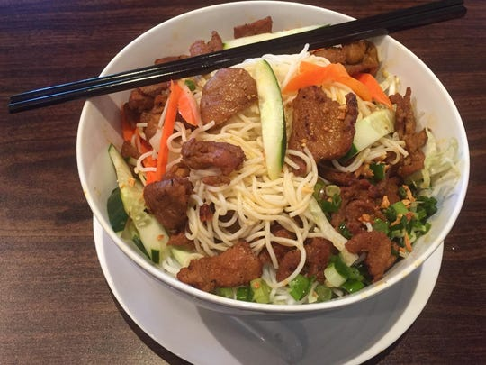 The rice noodle dishes include this snarl of noodles topped with charbroiled pork.