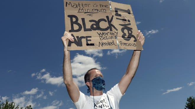 Matt Emond holds a sign during a Black Lives Matter protest on Saturday in the East Boston neighborhood of Boston.