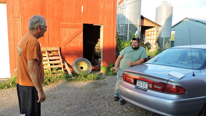 Larry Moore, left, and Mike Teeter talk dairy farming on a warm summer evening.