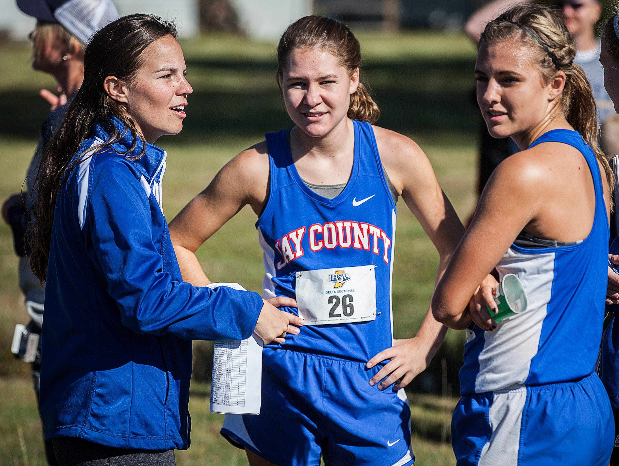 Coach Leah Wellman chats with her team after competing in the cross country sectional at the Sportsplex in Muncie on Saturday, Oct. 10, 2015.