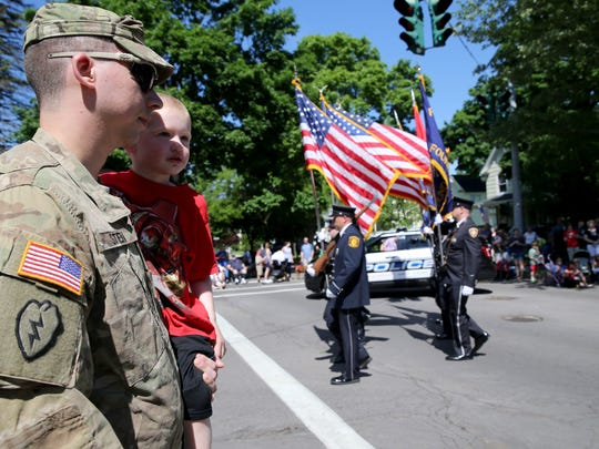Army veteran Michael Stein holds his nephew, Mason Smith, during the Fairport Memorial Day parade in 2017.
