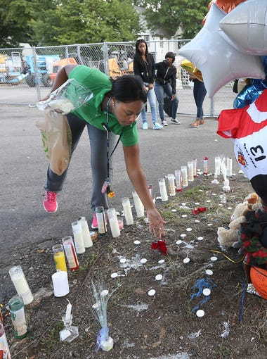 Alexis Land leaves rose petals at a memorial for her friend Raekwon Manigault before a  prayer during a vigil at the site of a drive-by shooting on Genesee St. that left 3 dead and 4 injured.