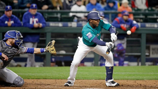 The Mariners' Guillermo Heredia bunts for single against Texas earlier this season.