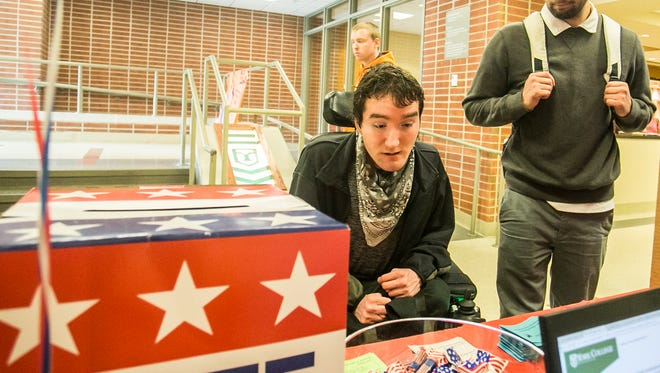 York College sophomore Tristan Schilling, left, of Glen Rock and HACC second year nursing student Christian Samoyedny, of Millersburg, take a look at the voting ballots for the York College mock election Tuesday, Oct. 4, 2016. Amanda J. Cain photo
