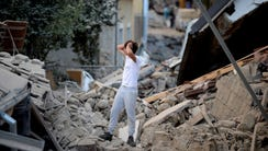 A man stands among damaged buildings after a strong