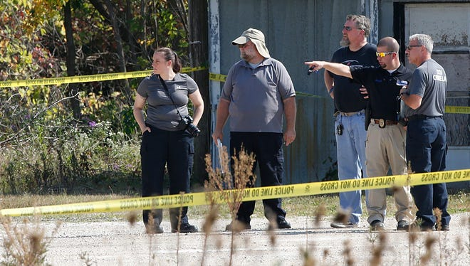Fond du Lac detective Bill Ledger points to an area where a body was found Sept. 23 in Fond du Lac.