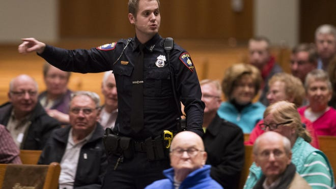 Fond du Lac Police Officer Erik Foster speaks to a group of about 100 people at Holy Family Catholic Community in Fond du Lac about what to do if someone starts shooting.