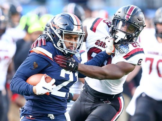 Virginia Cavaliers safety Juan Thornhill (21) returns an interception in the fourth quarter against South Carolina Gamecocks wide receiver Chavis Dawkins (83) in the 2018 Belk Bowl last December in Charlotte.