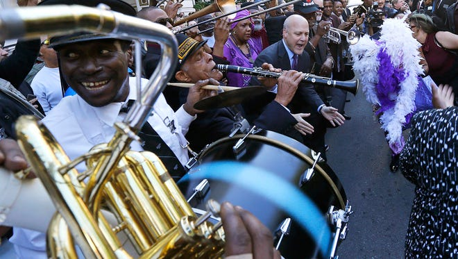 New Orleans Mayor Mitch Landrieu, top right, dances as jazz musicians perform a second line after a funeral tribute to New Orleans songwriter, producer and recording artist Allen Toussaint  in New Orleans, Nov. 20, 2015. Being mayor of the crescent City comes with a bit of celebrity status, and this fall's race is already drawing plenty of interest with Landrieu unable to run due to term limits. (AP Photo/Gerald Herbert)