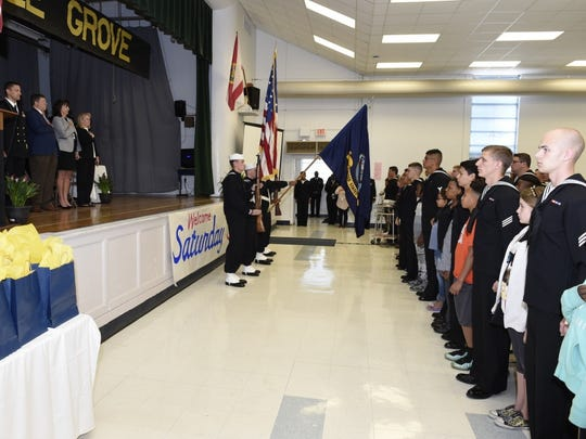 Attendees and participants of Myrtle Grove Elementary School's Saturday Scholars graduation ceremony honor the national anthem during opening events. Information Warfare Training Command Corry Station staff and students continued a long tradition of partnering with the Escambia County School District and volunteer mentors spent five Saturday mornings mentoring students in several core subjects.