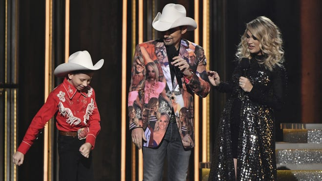 Mason Ramsey, left, floss dances as hosts Brad Paisley and Carrie Underwood look on at the 52nd annual CMA Awards. The dance spawned videos for how to do it — and to shame those who couldn't.