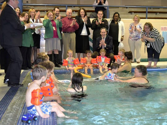 Owen McLean, 3, jumps into the arms of YWCA of Greater