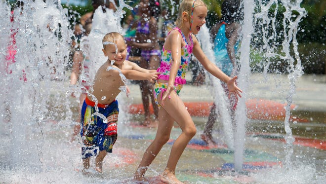 "Konrad Arnold (left), 4, plays with his sister, Reid, 6, while visiting the fountain at Royal Palm Pointe Park in Vero Beach. ""This is our first time here,"" said the siblings' mother Janet. ""They're having a great time. We're definitely going to take advantage of this."""