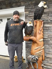 Don Mesuda, a chainsaw carver, pictured with one of