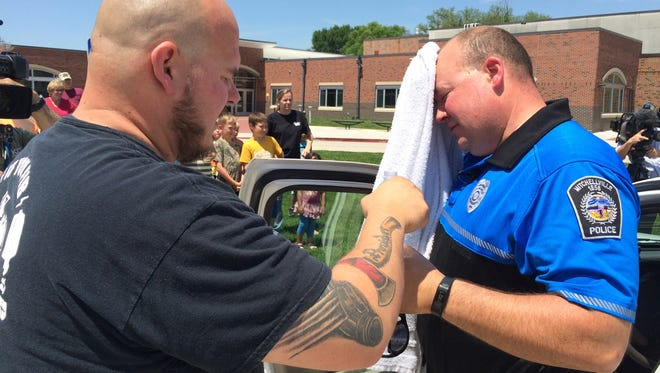Emergency medical technician Matt Cleverley, left, helps School Resource Officer Jeremy Stevenson of the Mitchellville (Iowa) Police Department cool down after he stayed 30 minutes in a hot car in June 2015.