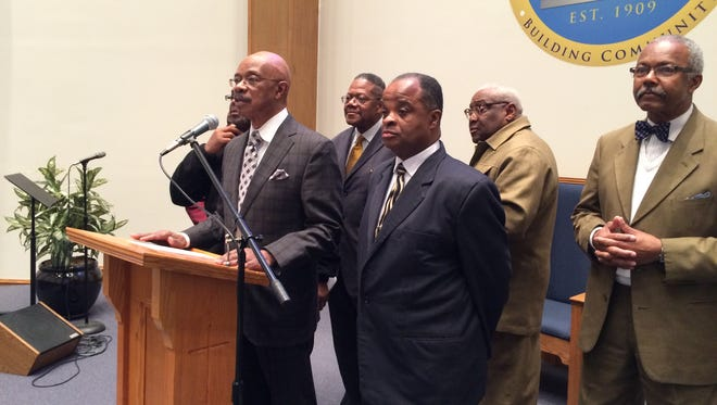 The Rev. Melvin T. Jones speaks at a press conference Thursday morning, surrounded by other clergy. Lansing churches are donating bottled water to Flint.