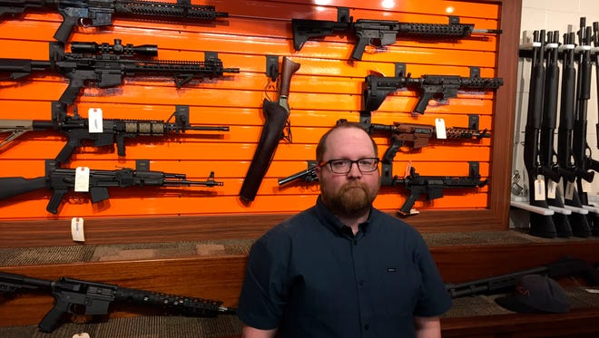 Josh O'Neal, general manager of the Rocky Mountain Gun Club in Grand Junction, Colorado, stands in front of a display of firearms at the state-of-the-art shooting range. O'Neal says safety is a high priority at the facility, but he and his staff are apprehensive regarding the possibility that a suicidal person might rent a gun at the site and then kill themselves.