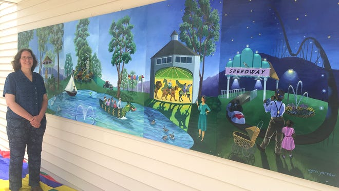 Elmira artist Aleta Wynn Yarrow shows off the mural she created to liven up the front of the Eldridge Park restroom building.