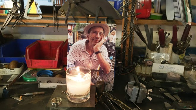 A candle-lit photo of jewelry artist Timothy Grannis, who died Sept. 6, 2016, sits Saturday at his work bench on Howard and Pine Streets. Photographed Sept. 10, 2016.