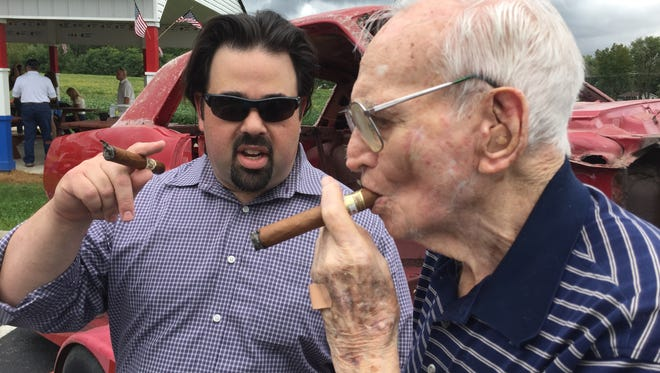 WIBC-FM (93.1) radio host Tony Katz, left, shares a cigar with World War II veteran Harry Donovan at a fundraiser Katz and the Danville American Legion hosted Saturday. More than $4,000 was raised to help restore Donovan's 1967 Mustang.