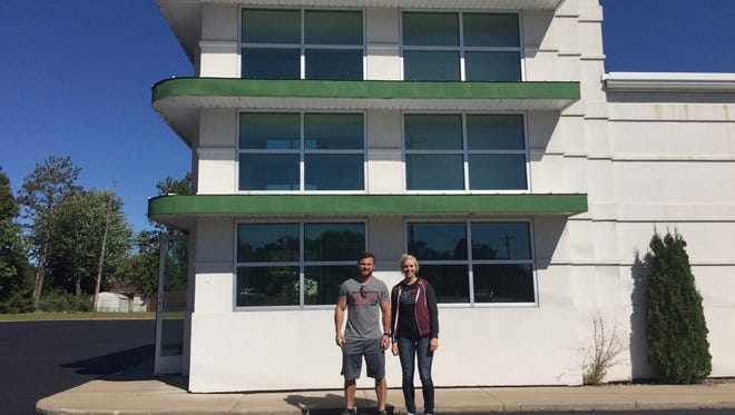 Coach Chris Stroik and manager Brook Haakenson stand in front of the building that will be Lift Athletic's newest gym. The building was formerly Dollar Mountain.