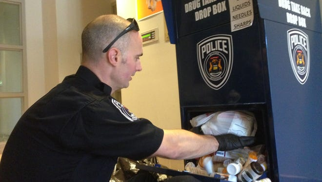 Milford Police Officer JD Panza cleans out a full drug take back box in the lobby of the police station. The program has become very popular in the Huron Valley.