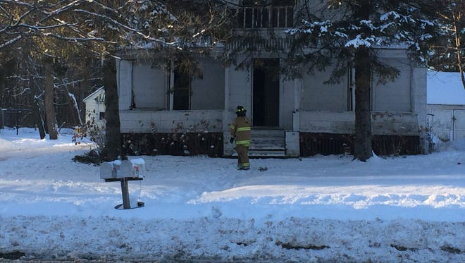 A firefighter stands in front of a duplex in the 900 block of Second Avenue where a fire sent one person to the hospital Wednesday afternoon.