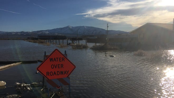 Snow-covered Peavine Mountain looms over a flooded neighborhood on the northern outskirts of Reno. Projections from Desert Research Institute that as much as 3,800 acre-feet of water could be released from the mountain in the form of snowmelt. Emergency responders say flood barriers are sufficient to handle the water.