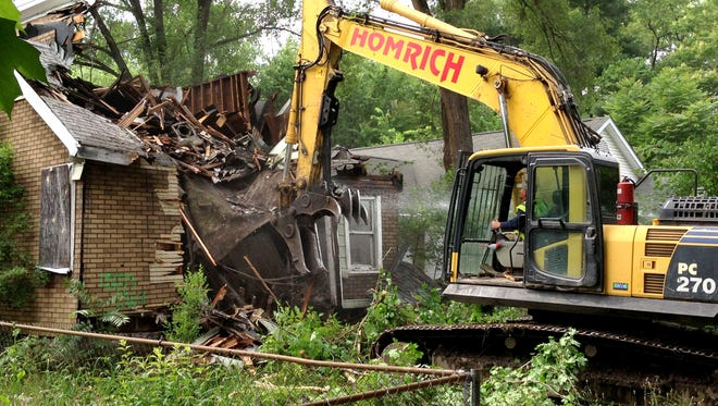 A contracted demolition crew from Detroit-based Homrich demolishes a house on Dolphin Street, as part of the city's blighted house demolition program in 2015.