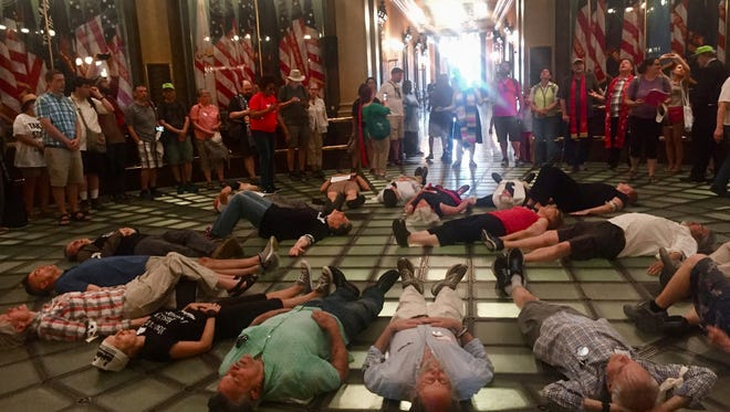 Protesters for the Michigan Poor People's Campaign lie down on the rotunda of the Michigan capitol Tuesday, May 29, 2018, in Lansing, Mich., as part of a die-in to protest war and militarism. Nineteen were arrested and received trespassing citations for not leaving when ordered.