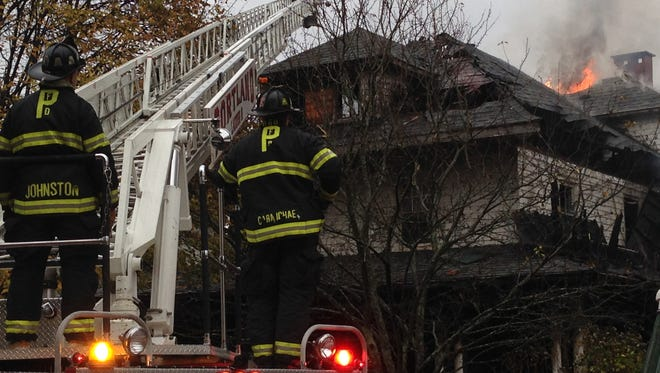 Firefighters work to douse a fire that killed five people and injured at least one other person Saturday in Portland, Maine.