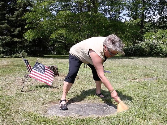 Barb Palmer, of Greece, sweeps the head stone of her