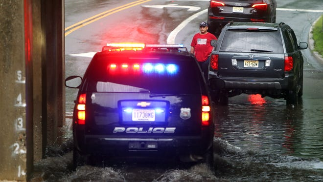 Police arrive after a cars engine flooded after driving under a flooded railroad trestle after a powerful afternoon storm took down power lines and trees leaving many without power. July 30, 2016, Morris Plains, NJ